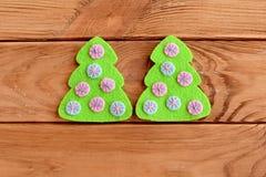 El verde sentía el árbol con las bolas rosadas y azules en un fondo de madera El fieltro del árbol de navidad cose Adorno del lib Imagen de archivo