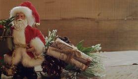 El verdor siguiente permanente de Santa Claus con madera abre una sesión un paquete en un fondo de madera imagenes de archivo