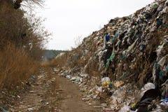 El vertido en Ucrania, pilas de plástico descargó adentro Los caminos a lo largo del revoltijo inútil inorgánico imagen de archivo