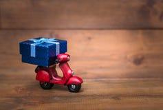 El vespa rojo de la motocicleta está transportando la caja de regalo azul Fotos de archivo
