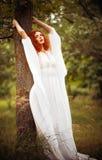 El vestido blanco que lleva de la mujer encantadora del pelirrojo coloca el árbol cercano fotos de archivo