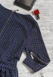 El vestido de las mujeres con la manga larga, la tableta y el esmalte de uñas rojo en una superficie de madera ligera Foto de archivo libre de regalías
