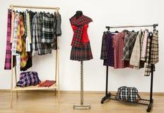 El vestido del armario con ropa de la tela escocesa arregló en suspensiones y un equipo en un maniquí. Imagenes de archivo