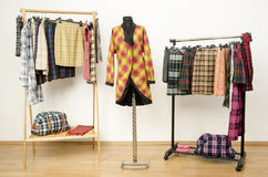 El vestido del armario con ropa de la tela escocesa arregló en suspensiones y una capa en un maniquí Foto de archivo libre de regalías