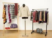 El vestido del armario con ropa de la tela escocesa arregló en suspensiones y una chaqueta en un maniquí Imagen de archivo