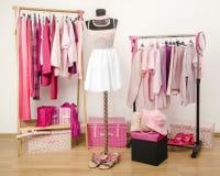 El vestido del armario con ropa rosada arregló en caída Imagen de archivo libre de regalías