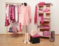 El vestido del armario con ropa rosada arregló en las suspensiones y el estante, una capa en un maniquí Fotos de archivo