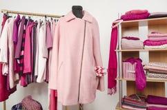 El vestido del armario con ropa rosada arregló en las suspensiones y el estante, una capa en un maniquí Foto de archivo