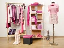 El vestido del armario con ropa rosada arregló en suspensiones y estante. Imagen de archivo