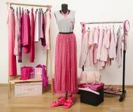 El vestido del armario con ropa rosada arregló en suspensiones y un equipo en un maniquí. Imagen de archivo libre de regalías