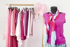 El vestido del armario con ropa rosada arregló en suspensiones y un equipo en un maniquí Imagen de archivo libre de regalías