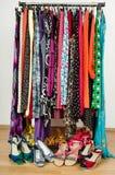 El vestido del armario con ropa y zapatos coloridos arregló agradable en un estante Foto de archivo