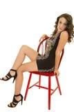 El vestido del cortocircuito de la mujer sienta las piernas rojas de la silla Fotografía de archivo