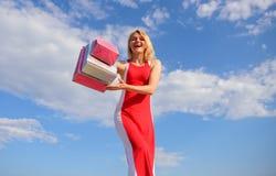 El vestido rojo de la mujer lleva el fondo del cielo azul de los panieres del manojo Marcas preferidas finalmente compradas Mucha imagen de archivo