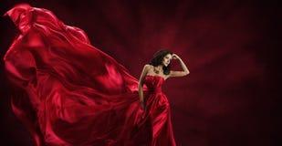El vestido rojo, mujer en la tela de seda de la moda del vuelo viste el modelo Foto de archivo libre de regalías