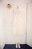 El vestido y los zapatos de la novia está colgando en la suspensión Imagen de archivo