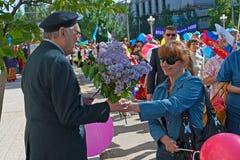 El veterano de la Segunda Guerra Mundial recibe enhorabuena de mujer en la demostración del primero de mayo en Stalingrad Fotos de archivo