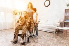 El veterano en una silla de ruedas se volvió del ejército Un hombre en uniforme en una silla de ruedas con su familia fotografía de archivo libre de regalías