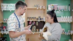 El veterinario de sexo masculino está aconsejando al dueño femenino joven del perro un forraje para su animal doméstico en una ti almacen de metraje de vídeo
