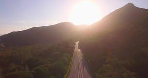 El viajar aéreo de la puesta del sol con un camino y las montañas almacen de metraje de vídeo