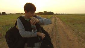 El viajar adolescente del muchacho Vagabundo adolescente del muchacho que camina a lo largo del camino en capilla con las mochila Imagen de archivo