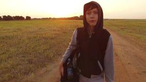 El viajar adolescente del muchacho Vagabundo adolescente del muchacho que camina a lo largo del camino en una capilla con las moc Foto de archivo libre de regalías