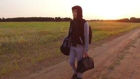 El viajar adolescente del muchacho Vagabundo adolescente del muchacho que camina a lo largo del camino en una capilla con las moc Fotografía de archivo