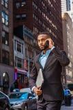 El viajar afroamericano joven del hombre de negocios, trabajando en nuevo Yor Imagen de archivo libre de regalías