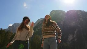 El viajar de la gente joven Dos mujeres jovenes que colocan en un fondo del las montañas y que se divierten almacen de metraje de vídeo