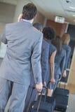 El viajar del aeropuerto de las empresarias de los hombres de negocios Fotografía de archivo libre de regalías
