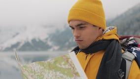El viajar en las montañas El caminante americano joven utiliza un mapa de papel del área Busca la trayectoria Disfruta de aventur metrajes