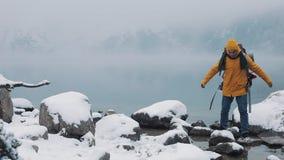 El viajar en las montañas Caminante de Americal que lleva la ropa amarilla del invierno que camina sobre piedras cerca del lago d almacen de video
