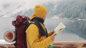 El viajar en las montañas El caminante joven utiliza un mapa de papel del área Busca la trayectoria Disfruta de aventura y de via metrajes