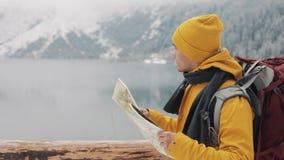 El viajar en las montañas El caminante joven utiliza un mapa de papel del área Busca la trayectoria Disfruta de aventura y de via almacen de video