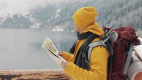 El viajar en las montañas El caminante joven utiliza un mapa de papel del área Busca la trayectoria Disfruta de aventura y de via almacen de metraje de vídeo