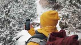 El viajar en las montañas Hombre joven que lleva la ropa amarilla del invierno que camina en el bosque cubierto con la película d almacen de video