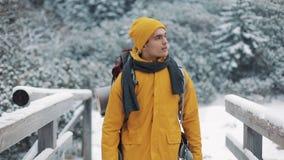 El viajar en las montañas Hombre joven que lleva la ropa amarilla del invierno que camina en la montaña cubierta con nieve Él va metrajes