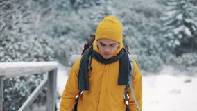 El viajar en las montañas Hombre joven que lleva la ropa amarilla del invierno que camina en la montaña cubierta con nieve Él va almacen de metraje de vídeo