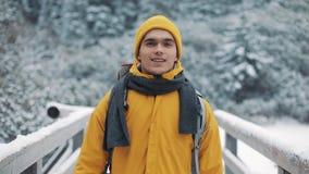 El viajar en las montañas Hombre joven que lleva la ropa amarilla del invierno que camina en la montaña cubierta con nieve Él va almacen de video