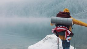 El viajar en las montañas Hombre joven que lleva la ropa amarilla del invierno que camina sobre piedras cerca del lago de la mont almacen de video