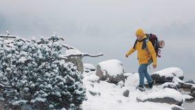 El viajar en las montañas Hombre joven que lleva la ropa amarilla del invierno que camina sobre piedras cerca del lago de la mont metrajes