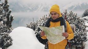 El viajar en las montañas Hombre joven que lleva la situación amarilla del mapa de la tenencia de la ropa del invierno en el bosq almacen de metraje de vídeo