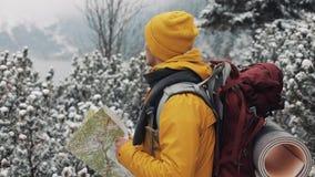 El viajar en las montañas Hombre joven que lleva la situación amarilla del mapa de la tenencia de la ropa del invierno en el bosq metrajes