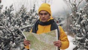 El viajar en las montañas Hombre joven que lleva el mapa amarillo de la tenencia de la ropa del invierno que camina en el bosque  almacen de video