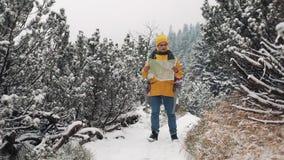 El viajar en las montañas Hombre joven que lleva el mapa amarillo de la tenencia de la ropa del invierno que camina en el bosque  almacen de metraje de vídeo