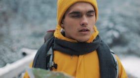 El viajar en las montañas Hombre joven que lleva el mapa amarillo de la tenencia de la ropa del invierno que camina en la montaña almacen de video