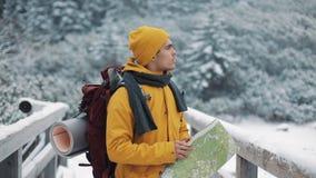 El viajar en las montañas Hombre joven que lleva el mapa amarillo de la tenencia de la ropa del invierno que camina en la montaña almacen de metraje de vídeo