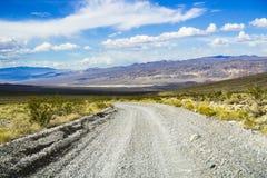 El viajar en un camino sin pavimentar con una área remota del parque nacional de Death Valley; montañas, cielo azul y nubes blanc fotos de archivo