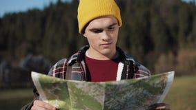 El viajar a las montañas El hombre del caminante celebra la vieja situación del mapa en el bosque y la mirada alrededor Los viaje almacen de video