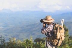 El viajar y fotografía Hombre joven con la cámara y la mochila TA fotos de archivo